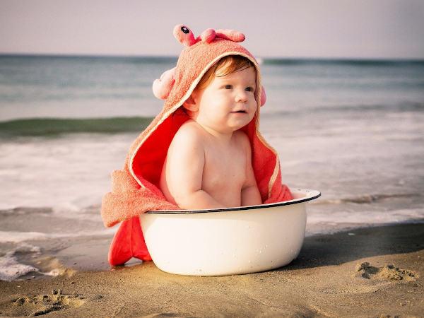 Kleinkind in einer Schüssel sitzend am Strand
