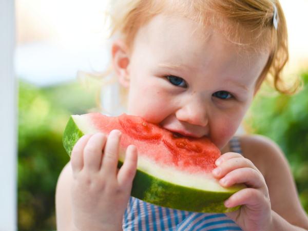 Ein Baby isst ein Stück Wassermelone.