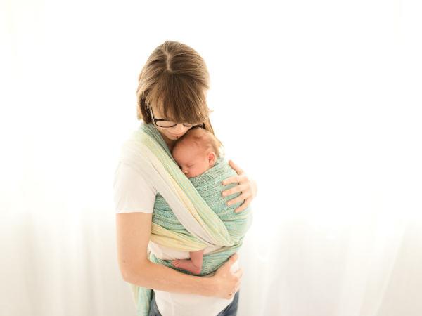 Natalie trägt ihre Tochter Mina in der Wickelkreuztrage.